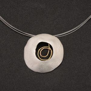 Colgante artesanal circular de plata y oro y detalle de oro